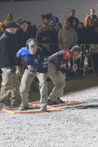 The two final competitors at the starting line for a head-to-head shoot off. Once the horn sounds, they run about 15 yards to their first shooting station. The winner will be the one who drops the last steel target first.