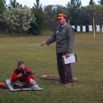 A Project Appleseed instructor works with a student shooting from the seated position.